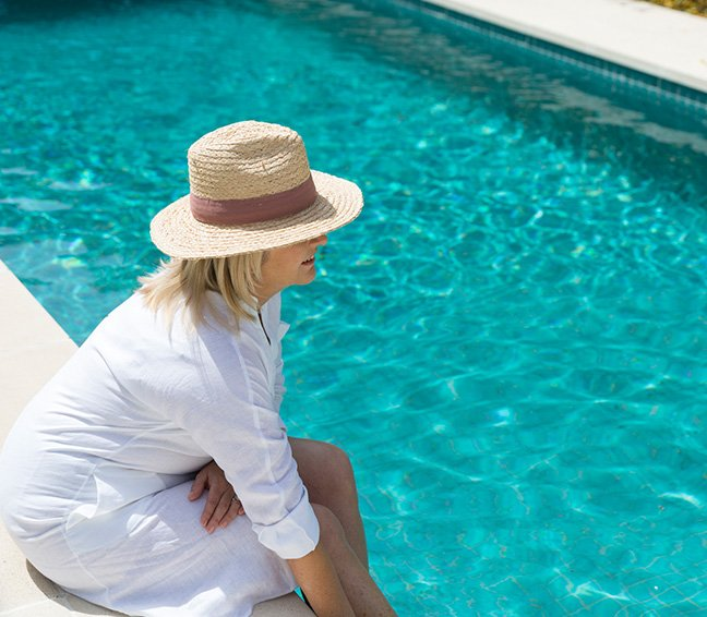 Woman, relaxing beside the lap pool, one of the many facilities at Pavilions.